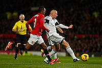 Saturday 11 January 2014 Pictured: Jonjo Shelvey gets the ball past Patrice Evra  of Manchester United<br /> Re: Barclays Premier League Manchester Utd v Swansea City FC  at Old Trafford, Manchester