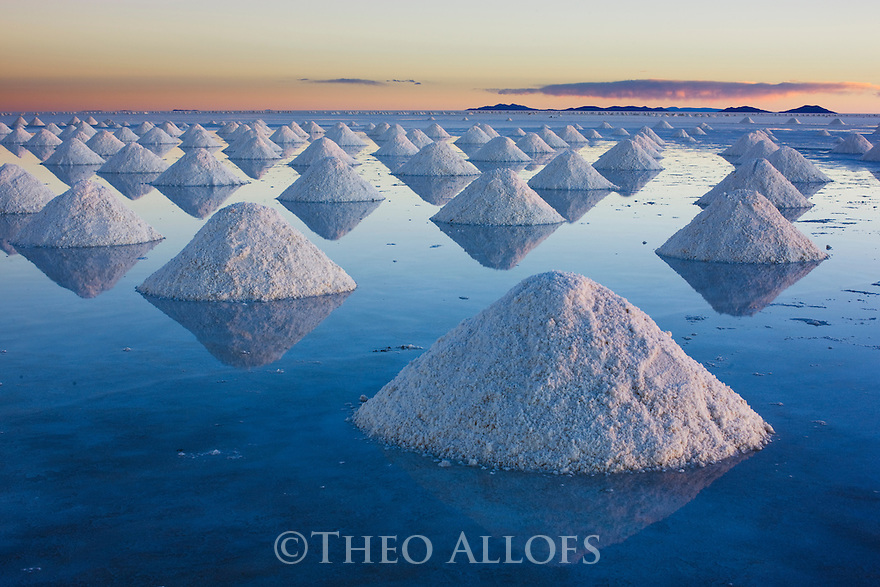 Bolivia, Altiplano, Salar de Uyuni, artificial salt mounts in Salar de Uyuni, largest salt pan in the world; the salt has been shoveled to mounts by salt workers for the salt to dry; sunset