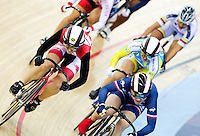 19 FEB 2012 - LONDON, GBR - Canada's Monique Sullivan (CAN) (on left in black and red) tries to get round the outside of the field during her Women's Keirin first round race at the UCI Track Cycling World Cup, and London Prepares test event for the 2012 Olympic Games, in the Olympic Park Velodrome in Stratford, London, Great Britain (PHOTO (C) 2012 NIGEL FARROW)
