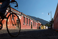 Local riding a bike down a street in Antigua, a UNESCO World Heritage Site in Guatemala