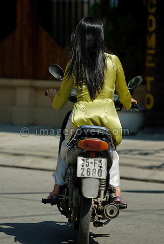 Asia, Vietnam, Hue. Elegant vietnamese woman riding a motorbike through Hue.