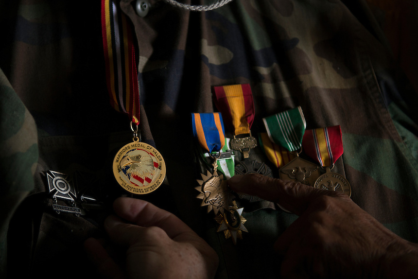 Tony Bush shows his military uniform adored with medals of honor from his military service in Vietnam. Tony keeps the uniform in the bathroom covered with bags and clothes and far from his eyes. Once a year he wear it to participate in the veteran's pow wow, organized by the Lakota tribe to celebrate the bravery of all Lakotas participated in different US wars.