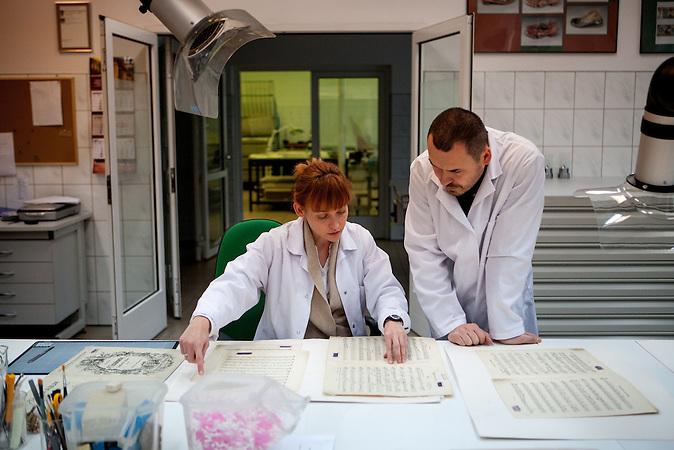 Nel Jastzebiowska (links, arbeitet seit 12 Jahren im Labor) und ihr Kollege Miroslow Maciaszczyk (seit 11 Jahren beschäftigt) im Labor zur Erhaltung von Dokumenten, Büchern und anderen historischen Zeugnissen. Momentan arbeiten sie an Notenblättern des Komponisten Tschaikowsky, die kürzlich gefunden wurden. Sie wurden vom Gefangenenorchester in Auschwitz benutzt. / Nel Jastrzebiowska (left, working since 12 Years in the lab) and her colleague Miroslaw Maciaszczyk (11 years employeed) at the Auschwitz  Museum Preservation lab for documents, books and other historical papers. At the moment the employees work on note sheets of composer Tchaikovsky which had been lately found and were used by the prisoners orchestra in Auschwitz. The Museum Preservation Department is responsible for protecting everything that remains at the Auschwitz-Birkenau Concentration Camp site.