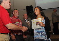 """NWA Democrat-Gazette/FLIP PUTTHOFF <br /> ESL CELEBRATION<br /> Bentonville High School student Carla Loyola gets a certificate and congratulations from school board members (from left) Brent Leas, Travis Riggs and Superintendent Mike Poore at the """"Exit Celebration"""" held Wednesday Sept. 16 2015 to recognize students who completed the school's English as a second language program. Thirty-one students received certificates of completion, said Ginger Mayes, English language development specialist for the Bentonville school district. Goals of the program include having students graduate bi-lingual or multi-lingual and be leaders in the school and community."""
