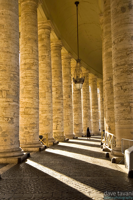 A lone nun walks through the pillars surrounding St. Peter's Square in the Vatican City.