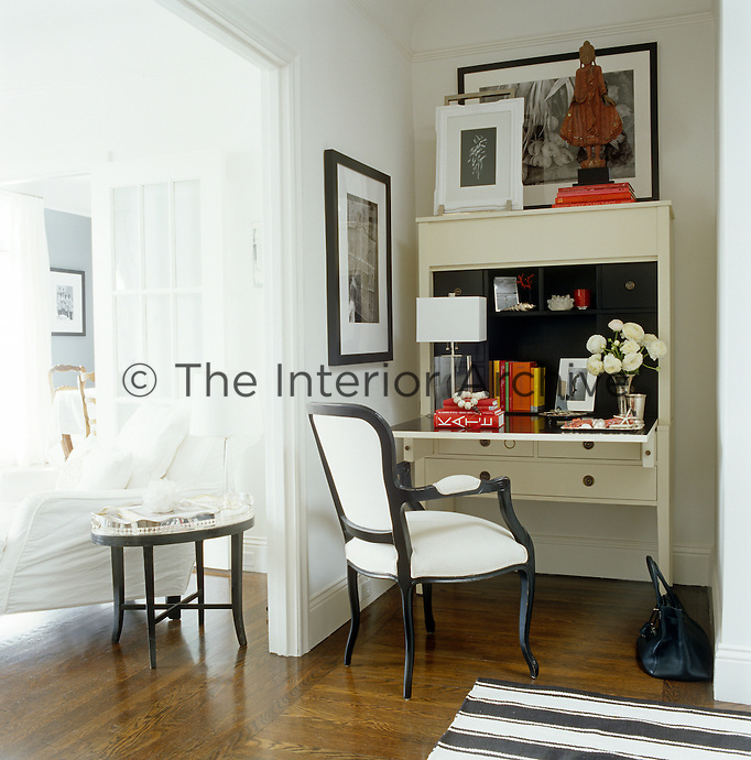 Tucked out of the way in a living room alcove an elegant bureau and linen-covered armchair create a compact home office