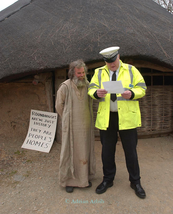 Leni Rickard shows a section 6 notice ( which prevents  him from being unlawfully evicted) to a police officer at a land occupation in the Pembrokeshire National Park - over 50 protesters occupied the buildings of  Castell Henlys, an iron age hill fort in protest against the decison of Pembrokeshire natl. park to  demolish  Tony Wrench's  low impact roundhouse whilst giving planning permission  to Bluestones holiday centre to build 340 holiday homes.