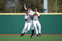(L-R) Charlie Cody (12), Ernie Clement (4), and Adam Haseley (7) of the Virginia Cavaliers celebrate their win over the Hartford Hawks at The Ripken Experience on February 27, 2015 in Myrtle Beach, South Carolina.  The Cavaliers defeated the Hawks 5-1.  (Brian Westerholt/Four Seam Images)