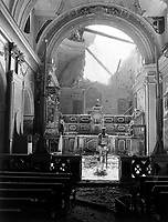 Pvt. Paul Oglesby, 30th Inf., standing in reverence before an altar in a damaged Catholic Church.  Note: pews at left appear undamaged, while bomb-shattered roof is strewn about the sanctuary.  Acerno, Italy.  September 23, 1943.  Benson. (Army)<br /> NARA FILE #:  111-SC-188691<br /> WAR &amp; CONFLICT BOOK #:  1033