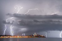 Lightnings storms strikes Rovinj in western Croatia. Like many other old European towns, it is popular with tourists for the cobblestone walkways, high walls and colorful buildings.  This photo shows the tall church spire of the Basilica of St. Euphemia.