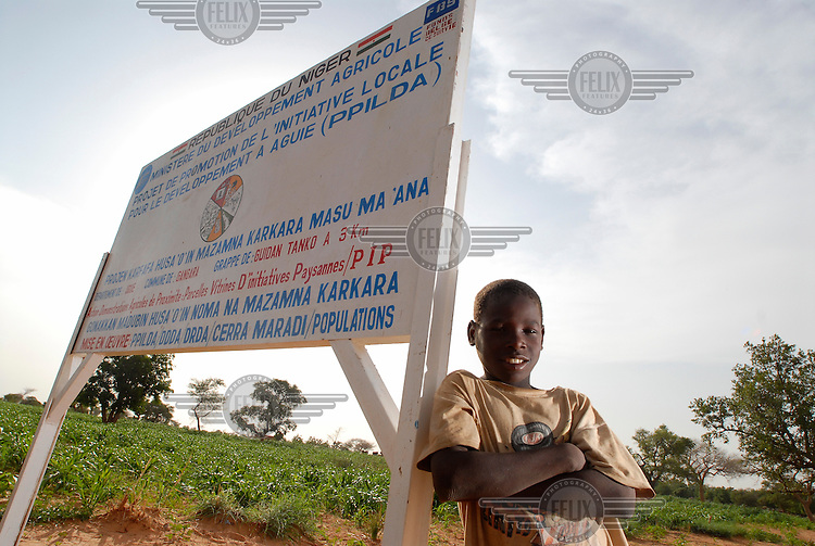 A young boy leans on a sign designating an IFAD Project for the Promotion of Local Initiatives for Development in Aguie (PPILDA) nursery site. The International Fund for Agricultural Development (IFAD), a specialised UN agency established to finance agricultural projects in developing countries, runs several programmes that work to combine environmental protection with agricultural productivity in the sub-Saharan Sahel region.