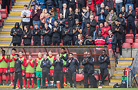 The Orient bench & staff behind join applause for Lifelong Orient supporter Frankie Bish who recently passed away during the Sky Bet League 2 match between Leyton Orient and Wycombe Wanderers at the Matchroom Stadium, London, England on 1 April 2017. Photo by Andy Rowland.