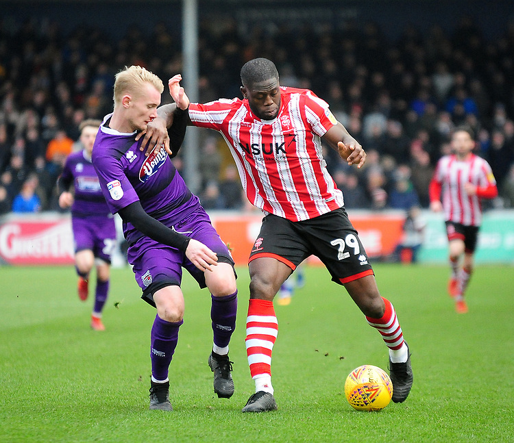 Lincoln City's John Akinde battles with Grimsby Town's Ludvig Ohman<br /> <br /> Photographer Andrew Vaughan/CameraSport<br /> <br /> The EFL Sky Bet League Two - Lincoln City v Grimsby Town - Saturday 19 January 2019 - Sincil Bank - Lincoln<br /> <br /> World Copyright &copy; 2019 CameraSport. All rights reserved. 43 Linden Ave. Countesthorpe. Leicester. England. LE8 5PG - Tel: +44 (0) 116 277 4147 - admin@camerasport.com - www.camerasport.com
