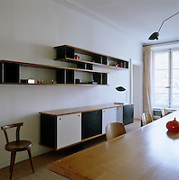 In the dining room a pair of Jean Prouve shelves and a long sideboard in retro 60s-style are constructed from wood with painted panels in black and white