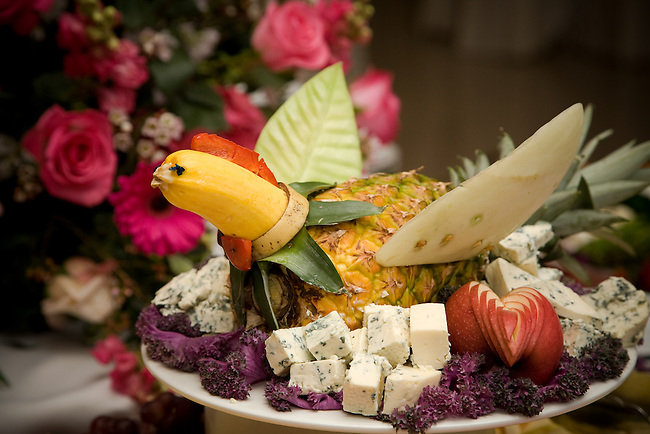 Food sculpture of  goose decorates fruit and cheese platter at cocktail party.