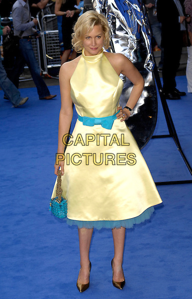 "ALICE EVANS.The UK Premiere of ""Fantastic Four: Rise Of The Silver Surfer"" at Vue West End Cinema, London, England. .June 12th 2007.full length yellow fifties style dres turquoise blue bow waistband belt bag bronze pointy shoes hand on hip.CAP/CAN.©Can Nguyen/Capital Pictures"