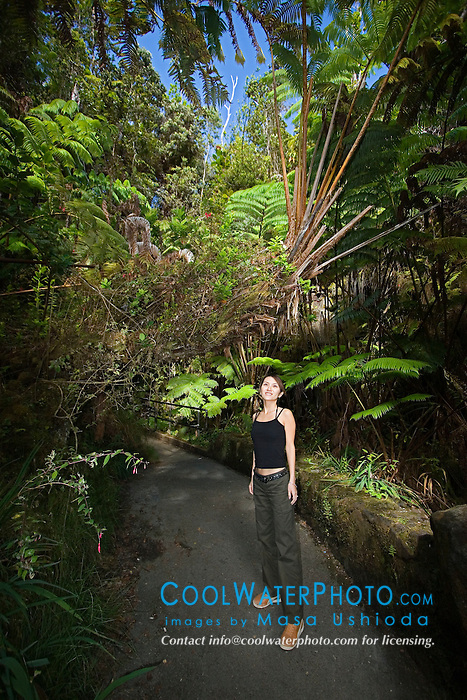 Woman visitor exploring tropical rainforest of Hapu`u Pulu or Fern Tree, Cibotium glaucum, and `Ohi`a Lehuna, Metrosideros polymorpha, Hawaii Volcanoes National Park, Kilauea, Big Island, Hawaii