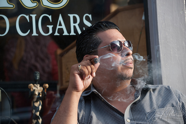 Cuban German Rivera enjoys a cigar on 7th Avenue in Ybor City today, Thursday 6/11/15.<br />