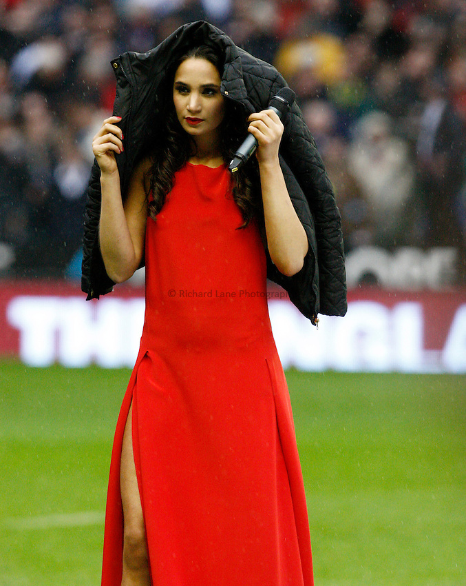 Photo: Richard Lane/Richard Lane Photography. England v South Africa. QBE Autumn Internationals. 24/11/2012. England's official anthem singer, Laura Wright shelters from the rain.