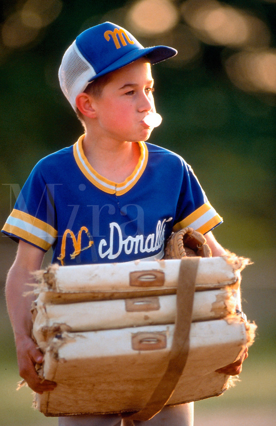 Boy in little league baseball uniform holding bases and blowing a bubble gum bubble.