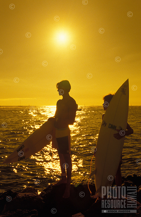 Two surfers holding their boards standing on lava rocks silhouetted against a golden setting sun.