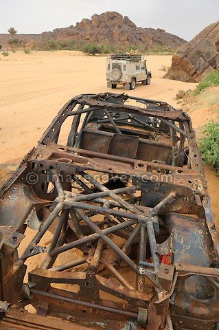 Africa, Mauritania, Sahara Desert, Rachid nr. Tidjikdja. Land Rover Defender TD5 Station Wagon behind the burnt out remains of a Paris Dackar race car at Rachid. --- No releases available. Automotive trademarks are the property of the trademark holder, authorization may be needed for some uses.