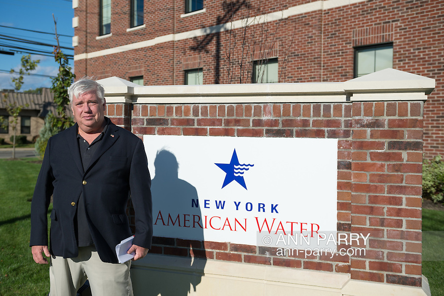 """Merrick, New York, USA. October 23, 2016. MICHAEL F. REID, the Democratic Party candidate for New York State Assembly District 14, poses at company sign outside the New York American Water Headquarter during environmental and civic groups' rally to demand public water and protest New York American Water's (""""NYAW"""") proposal to raise residents' water bills by 9.90%"""