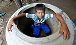 Ty Sona, 11, looks out from a large water jar in his village of Thmar Dat in northern Cambodia. Following devastating 2011 floods, Church World Service and Dan Church Aid, both members of the ACT Alliance, helped villagers to recover their homes and livelihoods.