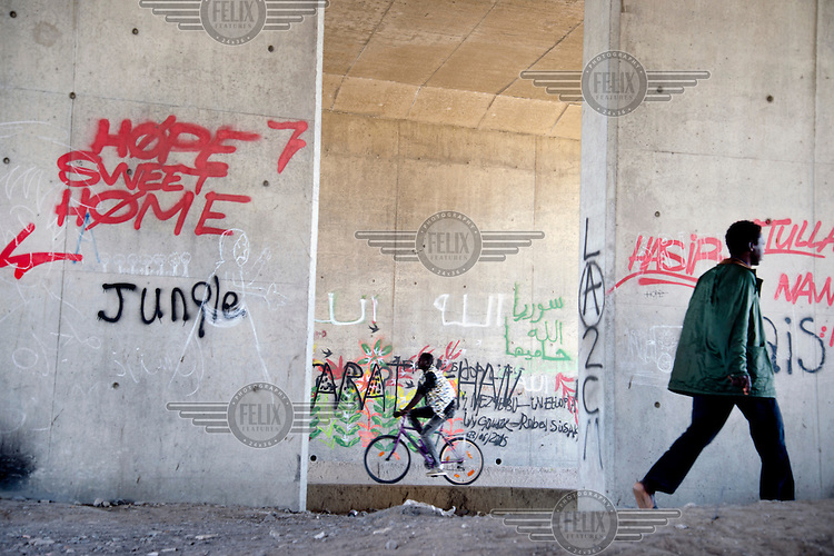 A pedestrian and a cyclist near the entrance to the so-called 'jungle' refugee camp located next to the motorway.