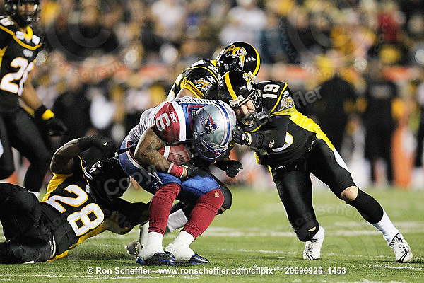 September 25, 2009; Hamilton, ON, CAN; Hamilton Tiger-Cats linebacker Jamall Johnson (28) and defensive back Sandy Beveridge (19) tackle Montreal Alouettes running back Avon Cobourne (6). CFL football: Montreal Alouettes vs. Hamilton Tiger-Cats at Ivor Wynne Stadium. The Alouettes defeated the Tiger-Cats 42-8. Mandatory Credit: Ron Scheffler. Copyright (c) 2009 Ron Scheffler.
