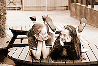 two girls friends lying on a wooden table at school looking at each other happily, London, United Kingdom Few years ago photographers Anthony Asael and Stepahnie Rabemiafara dreamed a dream that seemed quite imposible: to visit every country of the World promoting arts and tolerance among children and, of course, taking photographs of them. With little money and resources but an impressing will, the duo got an astonishing goal. In four years they visited 300 schools in 192 countries where kids participating of the project created 18,000 pieces of artwork. <br />