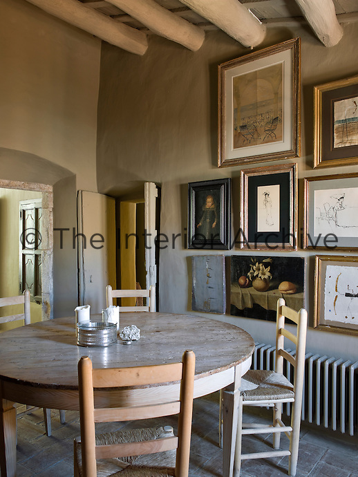 A collection of framed oil paintings and prints displayed on the dining room wall