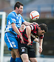 Queen of the South's Derek Young clears from Ayr Utd's Austin McCann.