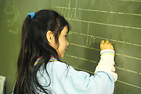Released, ethnic girl elementary school student practices handwriting on blackboard, California