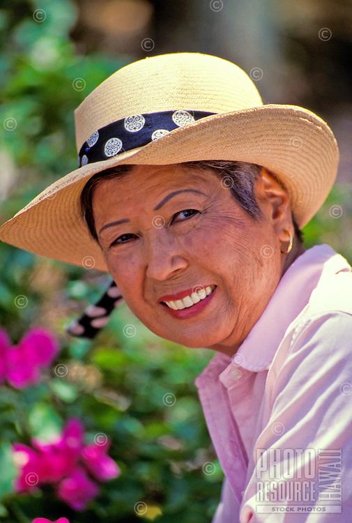 Portrait of an elderly asian woman in her yard