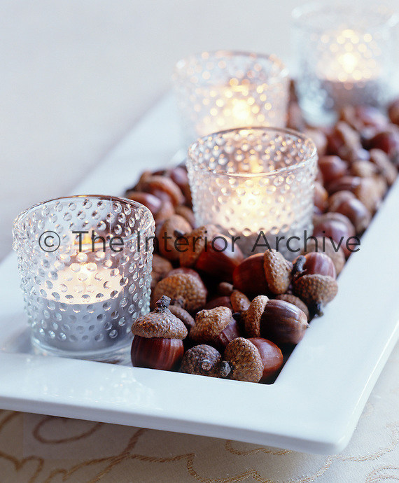 Tealights in glass containers on a bed of acorns creates a natural table decoration