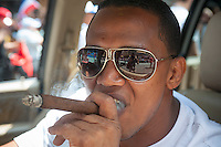 A cigar smoker participates in the Dominican Day Parade in New York on Sixth Avenue on Sunday, August 11, 2013.  Politicians, flags and cultural pride were on display at the annual event.  (© Richard B. Levine)