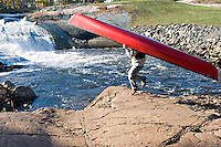 A solo canoeist does a dance move while portaging around a waterfall.