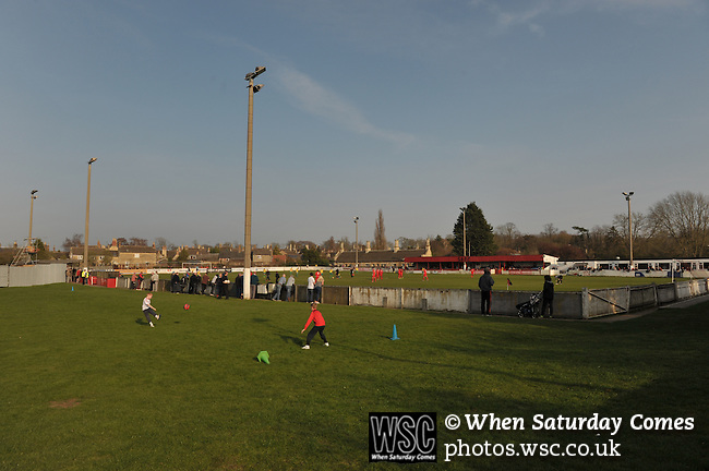 Stamford AFC 2 Marine 4, 29/03/2014. Wothorpe Road, Northern Premier League. Children playing football beside The Northern Premier League game between Stamford AFC and Marine from The Daniels Stadium. Marine won the game 4-2 in front of 320 supporters to boost their chances of relegation survival. Stamford AFC are moving to the brand new Zeeco Stadium at the end of the 2013/14 season Photo by Simon Gill.