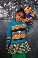 Khushi, 3, poses for a portrait with a soft toy in the Guria Non-Formal Education center in the middle of the Shivdaspur red light district, Varanasi, Uttar Pradesh, India on 20 November 2013. Guria uses the soft toys as a form of therapy for the children of the women in prostitution and also use it as signals of the children's emotional wellbeing.