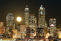 Full moon rising over Seattle city skyline at night, Seattle, Washington, US
