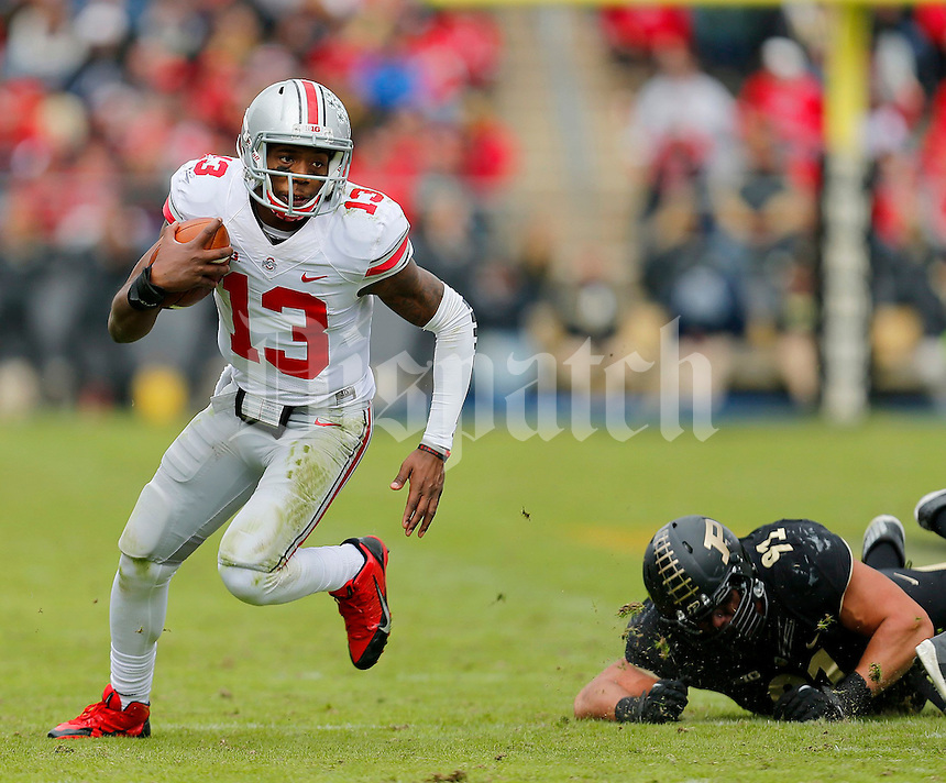 Ohio State Buckeyes quarterback Kenny Guiton (13) gets past Purdue Boilermakers defensive end Greg Latta (91) during the second half of the NCAA football game at Ross-Ade Stadium in West Lafayette, IN on Saturday, November 2, 2013. (Columbus Dispatch photo by Jonathan Quilter)