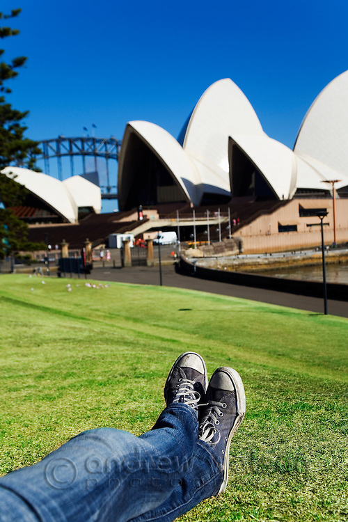Relaxing on the lawn of the Royal Botanic Gardens in front of the Sydney Opera House.  Sydney, New South Wales, AUSTRALIA.
