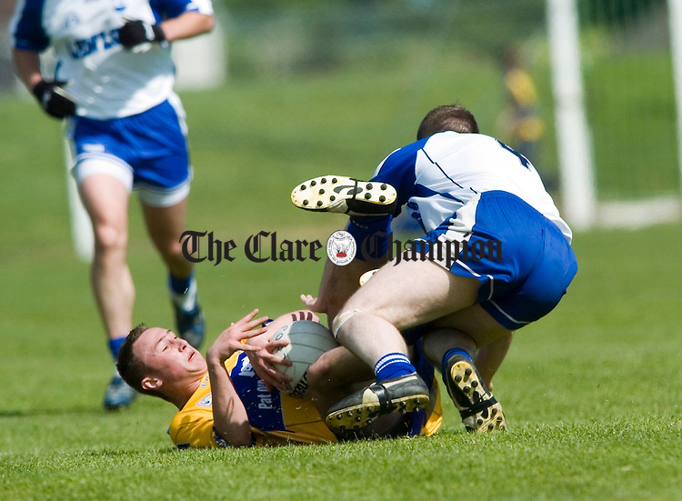 Clare's David Connole goes down under pressutre from Waterford's Shane Biggs during their senior championship game in Dungarvan. Photograph by John Kelly.