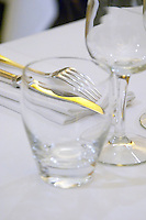 Knife and fork on a white linen napkin and table cloth, water class and wine glass in the restaurant Le Gourmandin in Beaune Cote d'Or Burgundy Bourgogne France Europe