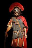 Model of a Roman centurion, an army officer in charge of the manoeuvres, conduct and training of a century of 80 men, wearing a plumed helmet and chainmail, in the Roman Army Museum, Hadrian's Wall, Northumberland, England. A centurion would wear a sideways horsehair crest on his helmet, a chainmail shirt over a leather doublet and a cloak on his back, with a sword and dagger at his belt. Hadrian's Wall was built 73 miles across Britannia, now England, 122-128 AD, under the reign of Emperor Hadrian, ruled 117-138, to mark the Northern extent of the Roman Empire and guard against barbarian attacks from the Picts to the North. The Roman Army Museum at Carvoran fort is run by the Vindolanda Charitable Trust and forms part of the Hadrian's Wall UNESCO World Heritage Site. Picture by Manuel Cohen