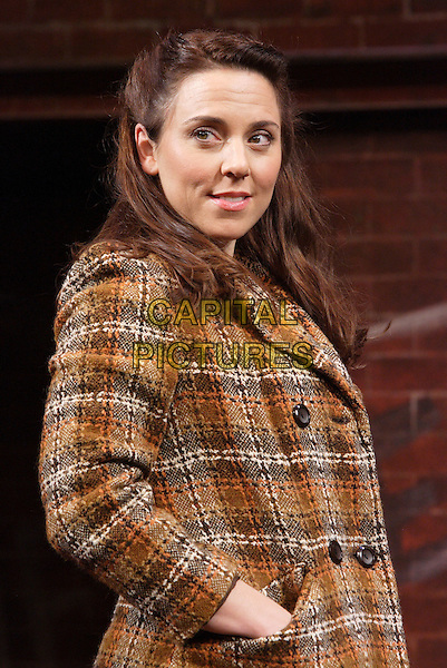 "MELANIE CHISHOLM (Mel C) as Mrs Johnston .""Blood Brothers"" photocall, Phoenix Theatre, London, England. .October 21st 2009.sporty spice scene acting on stage set costume musical half length brown orange plaid tweed coat black hands in pockets .CAP/ROS.©Steve Ross/Capital Pictures."
