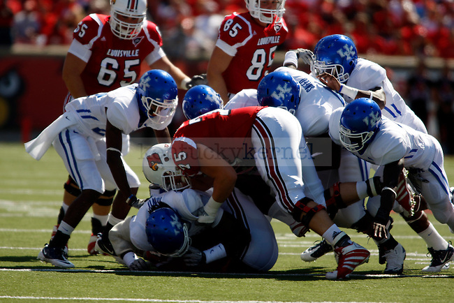 UK offense gets taken down by U of L defense in the first half of the UK's 23-16 win over U of L, kicking off Joker Phillip's reign as head coach on Saturday, September 5, 2010. Photo by Britney McIntosh | Staff