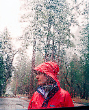 USA, California, Yosemite National Park, a young woman in red raincoat