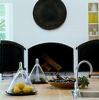 Beyond the central work surface in the kitchen is a traditional pizza oven